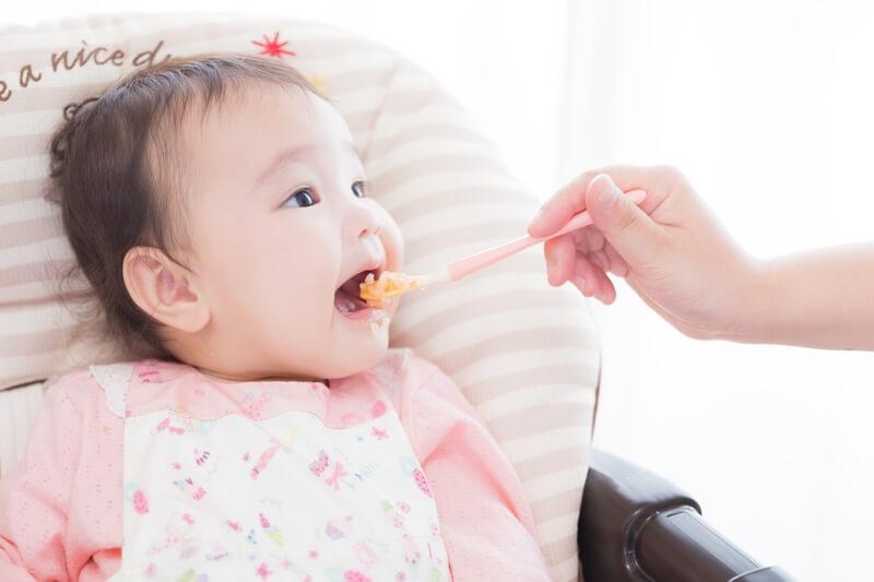 離乳食を食べさせる親